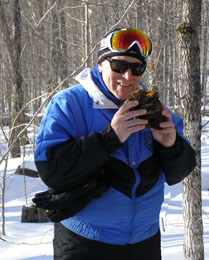 Edward, wearing Smith Optics Chief Sunglasses,  inspecting chaga while Snowshoeing in Mont-Tremblant - Photo by Luxury Experience