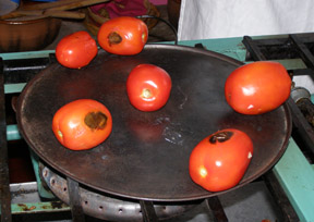 Tomatoes roasting on a comal